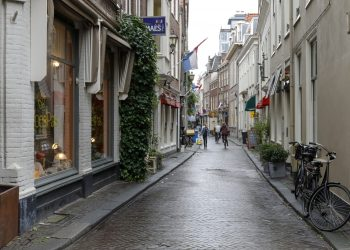 The Hague, The Netherlands - October 11, 2019: Narrow cobbled street in the old part of the city. On both sides of the street there are shops and restaurants and in the distance there are a few people. The Hague is locally called Den Haag and is the seat of the Dutch government, but not this city but Amsterdam is the constitutional capital of the Netherlands.